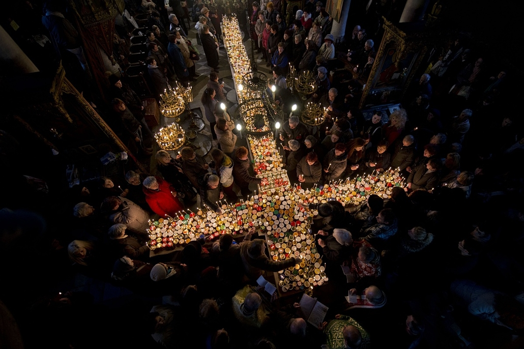 afp. hét képei - 2016.02.10. Bulgária, mézüzzenp, gyertya, kereszt, Believers pray around a cross-shaped platform covered with candles placed in jars of honey during a ceremony marking the day of Saint Haralampi, Orthodox patron saint of bee-keepers, at t